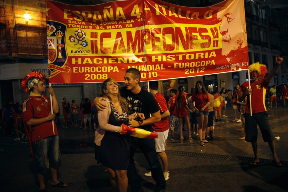 Spain's soccer fans hold a banner with the colours of the Spanish flag as they celebrate Spain's victory over Italy in their Euro 2012 final soccer match held in Kiev, in Malaga