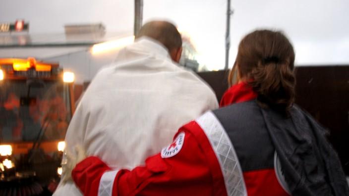 Sanitäter des Roten Kreuzes versorgen Betrunkenen auf dem Oktoberfest, 2008