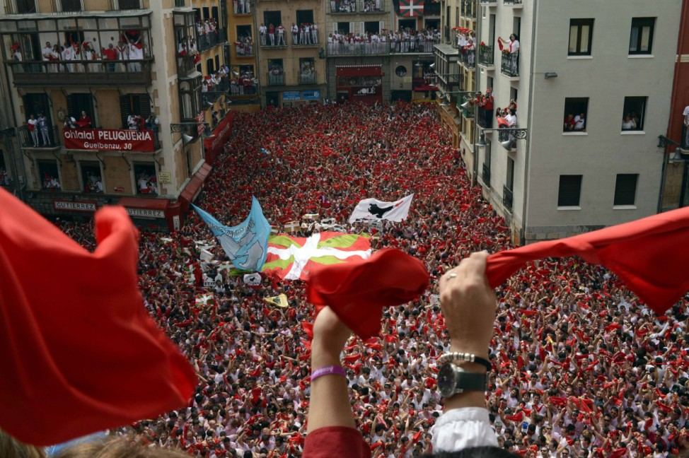 Revellers on the town hall balcony hold up red scarves during the start of the San Fermin Festival in Pamplona