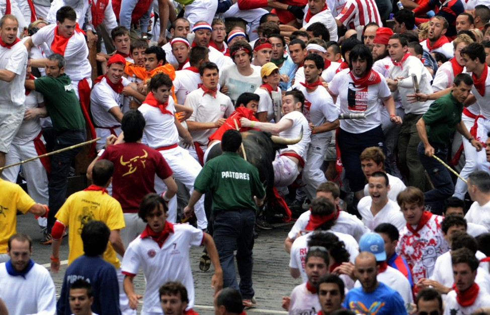 Fugado, a Cebada Gago fighting bull, charges at runners at the Telefonica corner during the third Encierro of the San Fermin festival in Pamplona