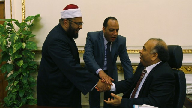 Parliament members greet parliament speaker Saad al-Katatni after a session at the parliament building in Cairo