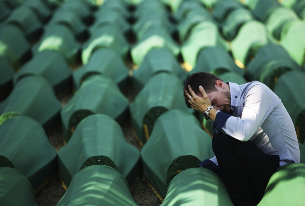 A Bosnian Muslim man sits and cries near the coffin of his relative at Memorial Center in Potocari before a mass burial, near Srebrenica