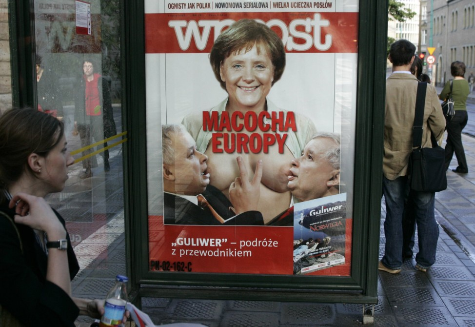 People wait at a tram stop next to an advertisement showing the cover of Polish weekly magazine Wprost in Poznan