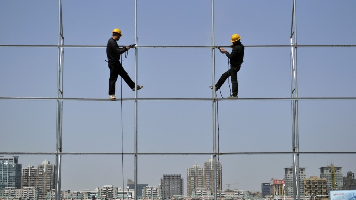File photo of workers standing on a steel frame, which they are welding for an advertising board, in Jiaxing