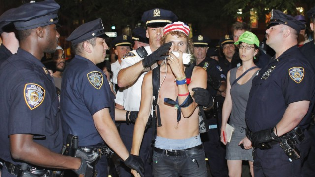 An Occupy Wall Street activist is arrested by New York police officers during a protest at Zuccotti Park in New York