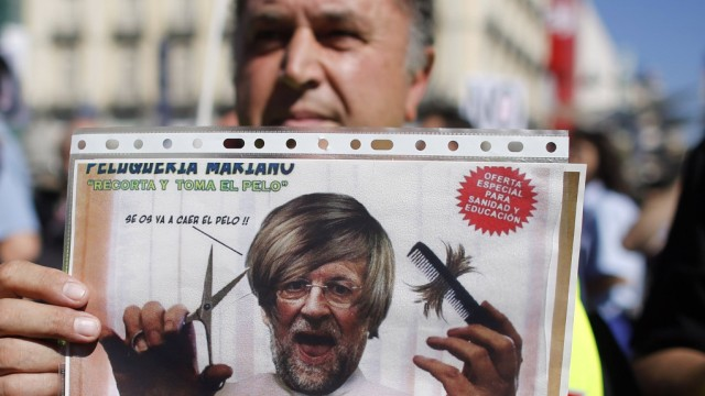 A civil service worker holds up a placard depicting a parody of Spain's Prime Minister Mariano Rajoy during a protest over government austerity measures at Madrid's landmark Puerta del Sol in front of city hall in Madrid