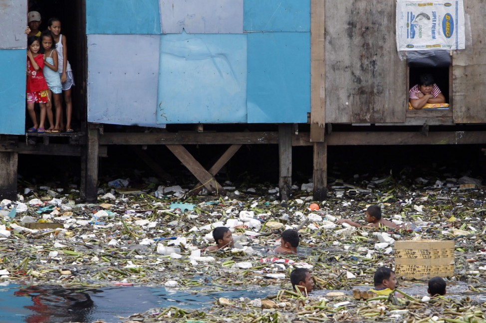 Informal settlers watch men gather recyclable materials from among the debris swept by strong winds off the murky waters in Manila bay