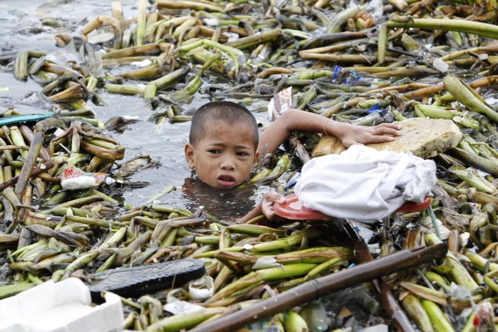 A boy holds his shirt on the lid of a plastic container to keep it dry while gathering recyclable materials from the debris swept by strong winds in Manila bay