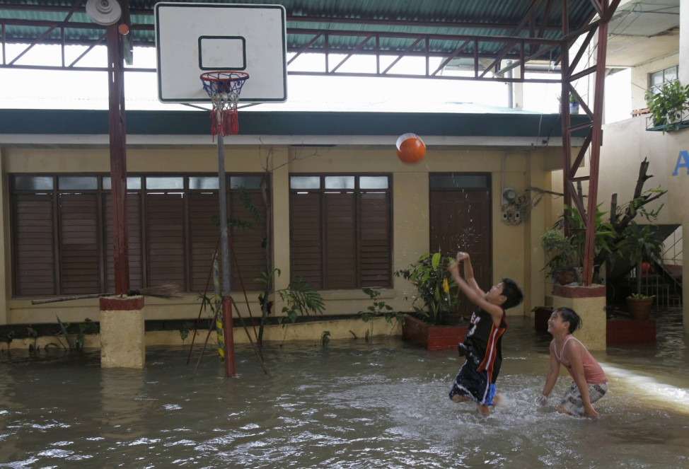 Boys play basketball at a school that is submerged in floodwaters brought by tropical storm Saola at Almacen town