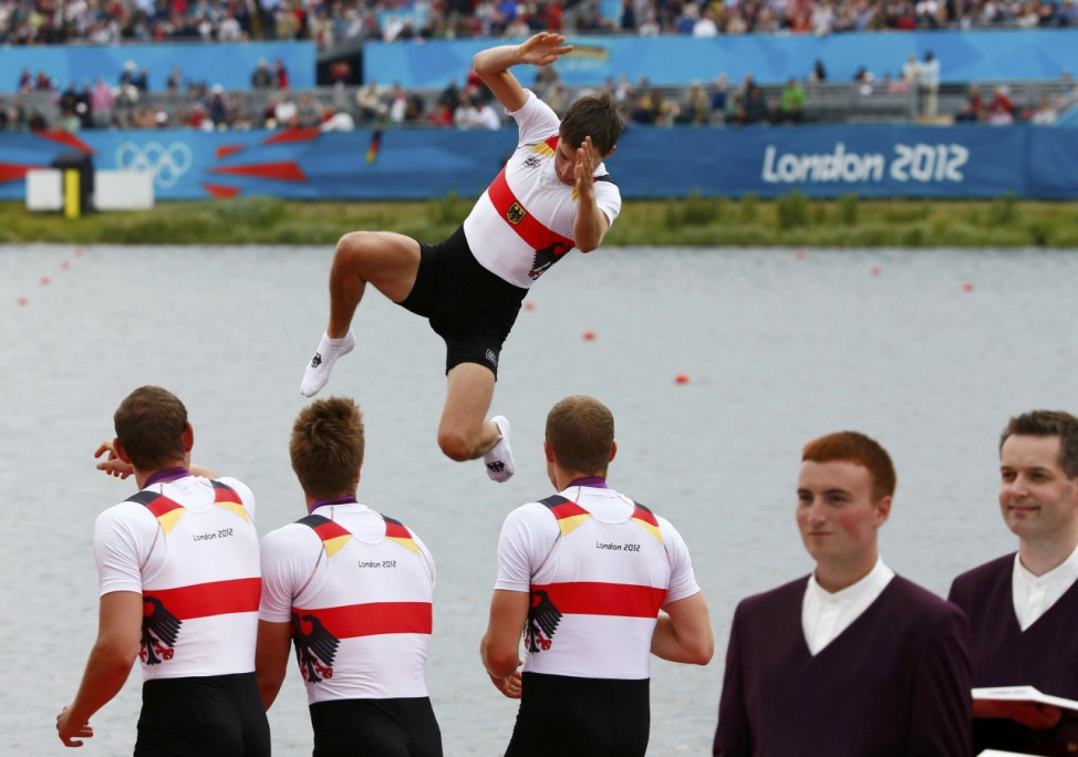 Team Germany celebrate winning the men's eight Final A by throwing a team mate into the water at Eton Dorney during the London 2012 Olympic Games