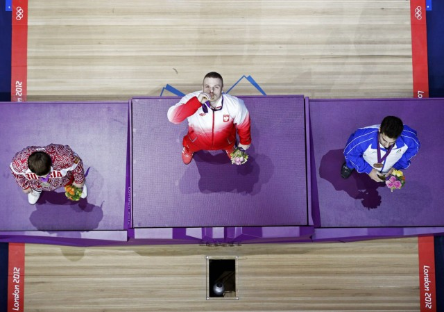 Poland's Adrian Edward Zielinski, Russia's Apti Aukhadov and Iran's Kianoush Rostami pose at the podium of the men's 85Kg weightlifting competition at the ExCel venue at the London 2012 Olympic Games