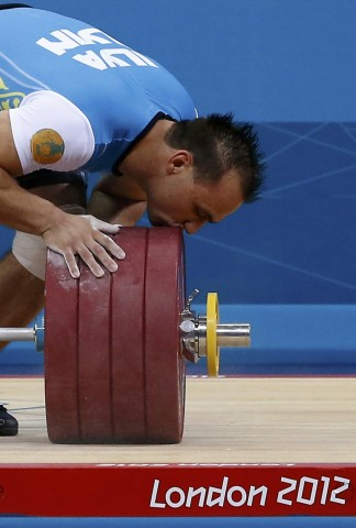 Kazakhstan's Ilya Ilyin kisses the weights after successful lift on the men's 94Kg group A weightlifting competition at the ExCel venue at the London 2012 Olympic Games