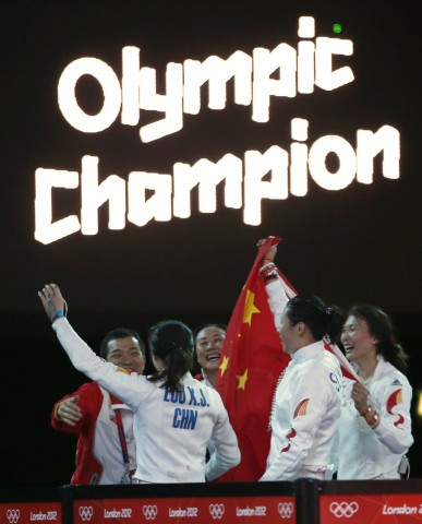 China's fencing team members celebrate their victory against South Korea after their women's epee team gold medal fencing competition at the London 2012 Olympic Games