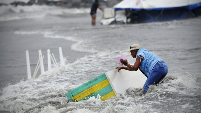 Woman tries to recover piece of furniture that is being washed away by flood in Boca Del Rio on the outskirts of Veracruz