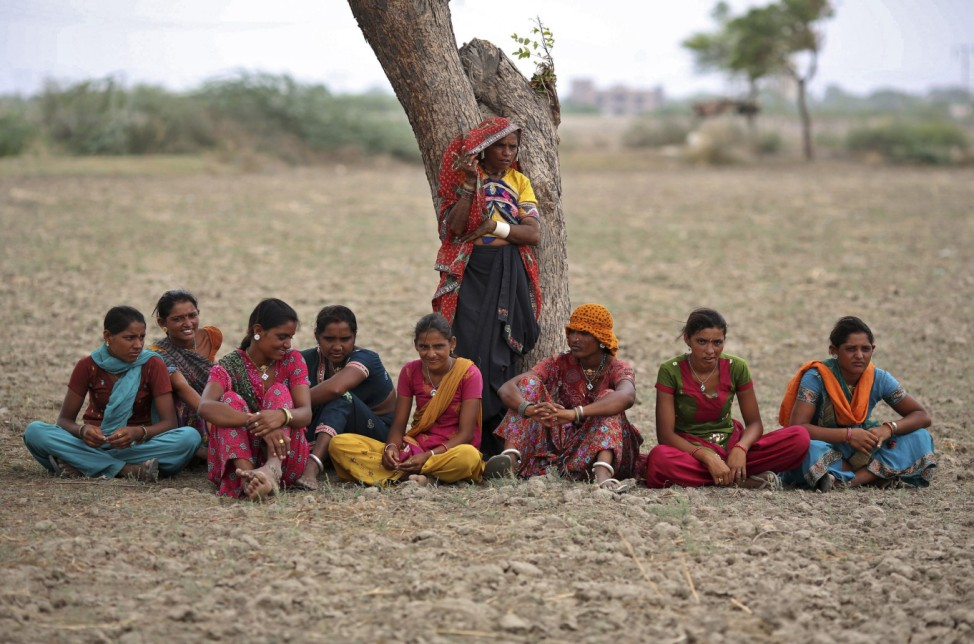 Village women rest under a tree as they migrated due to shortage of water on the outskirts of Sami town
