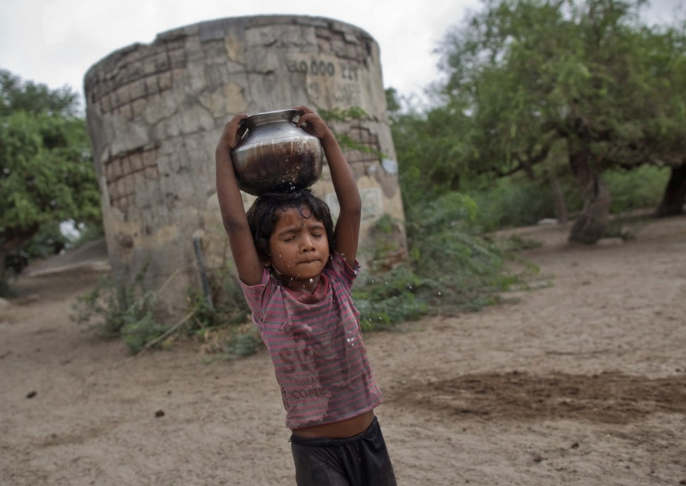 Joshiya carries metal pitcher filled with water from a near-by well at Badarganj village
