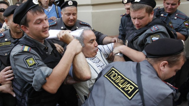 Police detain former world chess champion and opposition leader Kasparov during the trial of the female punk band 'Pussy Riot' outside a court building in Moscow