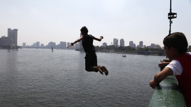 A boy watches another jump from a bridge to cool off in the river Nile during Eid al-Fitr in Cairo