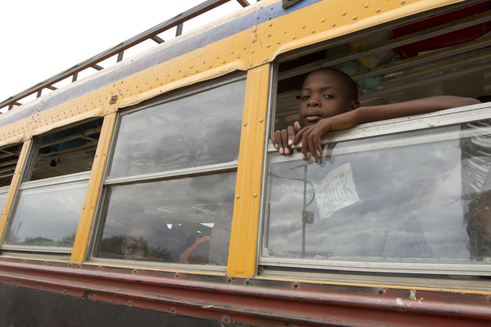 A child looks out of a bus window as residents of a camp for displaced people of the 2010 earthquake voluntarily evacuate in the wake of arriving tropical storm Isaac in Port au Prince