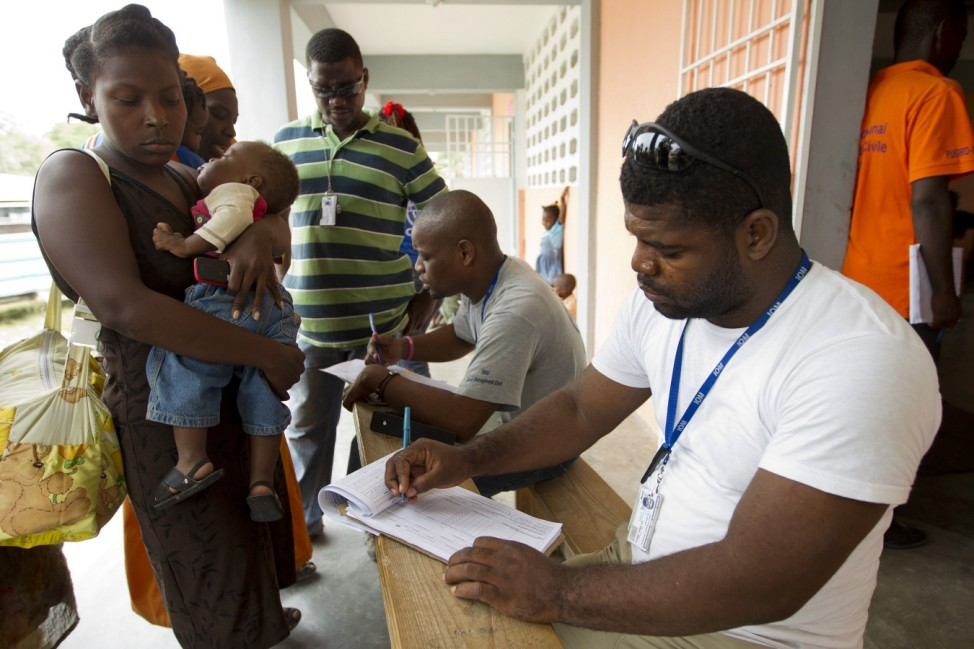 Members of the International Organization for Migration register displaced people who will be taking shelter at a school before the arrival of tropical Storm Isaac in Port au Prince
