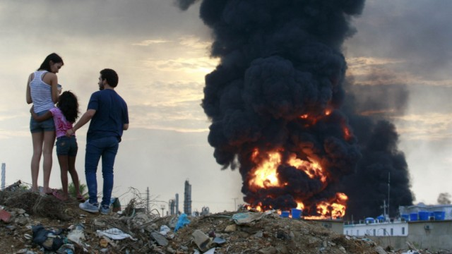 A family observes the fire in the affected area after an explosion at Amuay oil refinery in Punto Fijo in the Peninsula of Paraguana