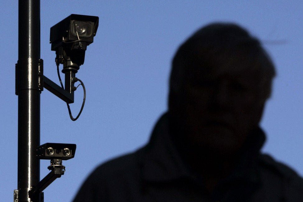 A security camera overlooks a man as he walks down a street in London
