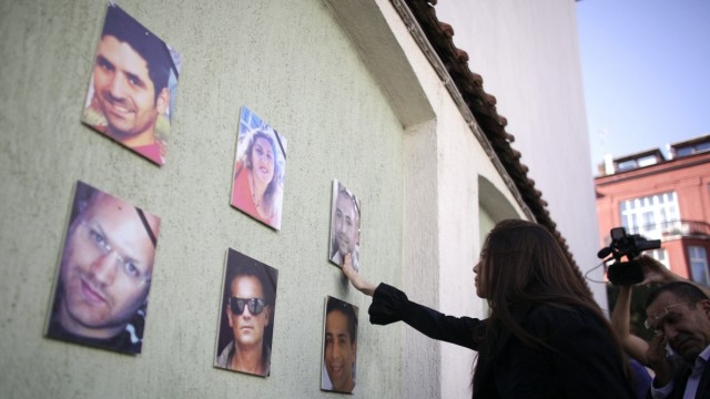 A relative touches the picture of a victim of last month's bomb attack before the start of a memorial service at the Sofia Synagogue
