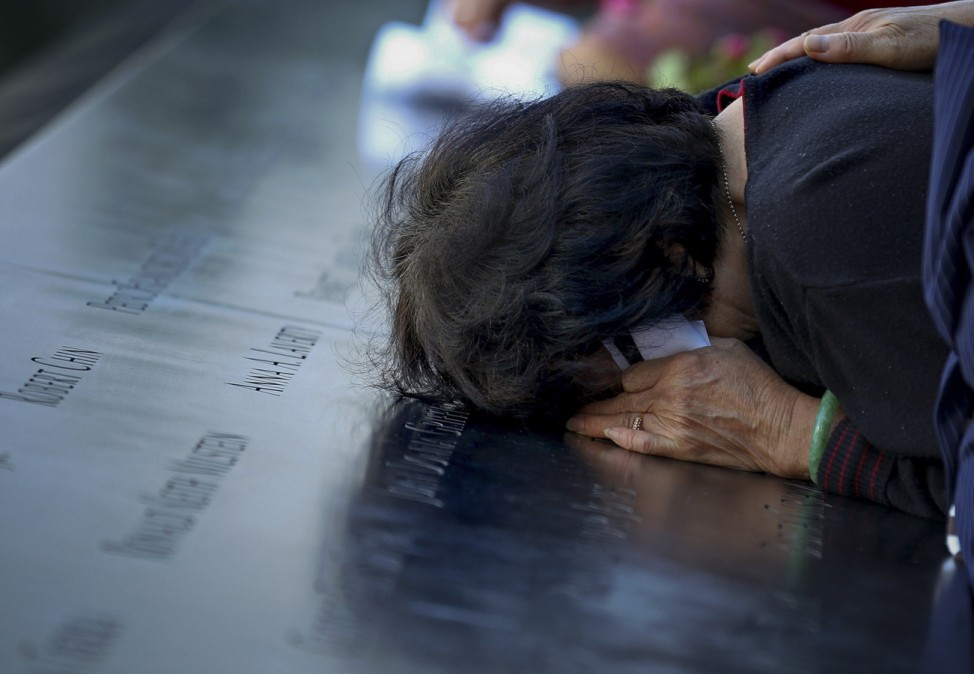 A woman weeps on the South Pool wall of the 9/11 Memorial during ceremonies marking the 11th anniversary of the 9/11 attacks on the World Trade Center in New York