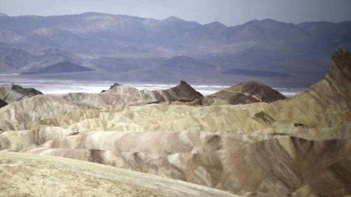 A man photographs a boy at Zabriskie Point in Death Valley National Park