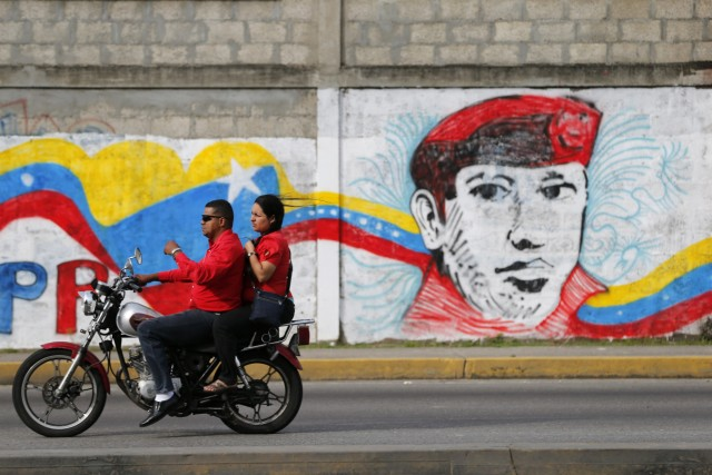 A motorcycle rides past a campaign mural promoting Venezuelan President Hugo Chavez in Barinas