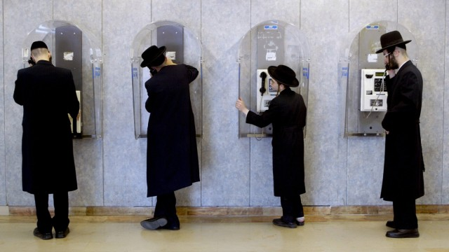Ultra orthodox Jews makes phone calls as they wait for their flight at the Israeli International airport of Ben Gurion during a nationwide general strike
