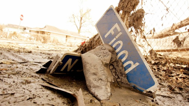 Street sign for Flood Street sits in the mud where it fell after Hurricane Katrina in New Orleans