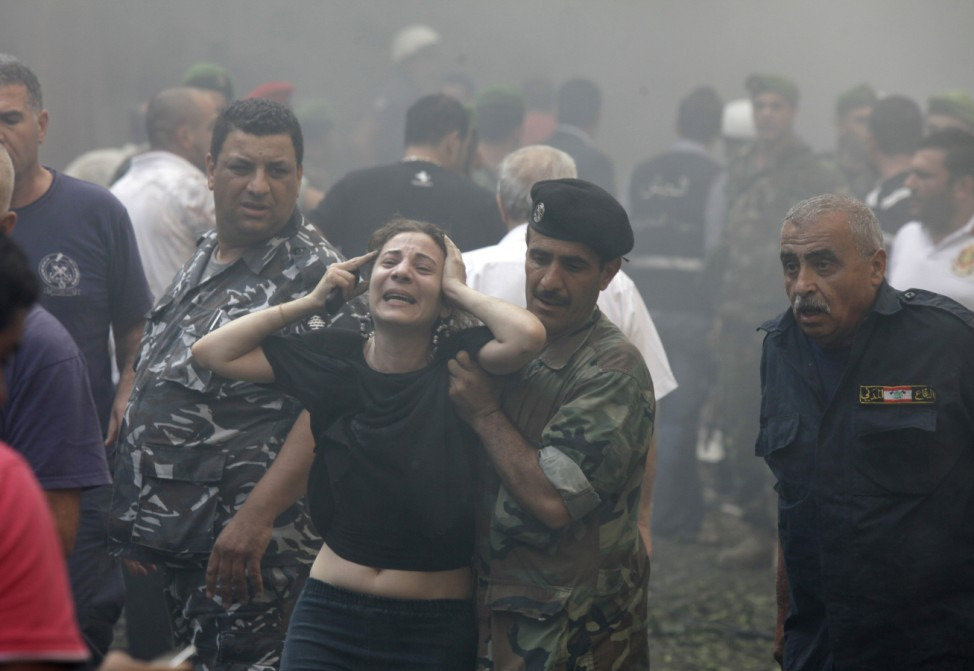 A woman is helped by a Lebanese soldier after an explosion in Ashafriyeh district