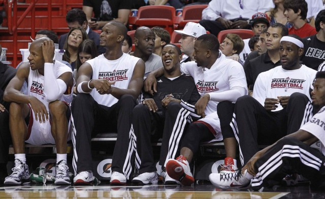 Miami Heat players look towards the action in their preseason NBA basketball game against the Detroit Pistons in Miami