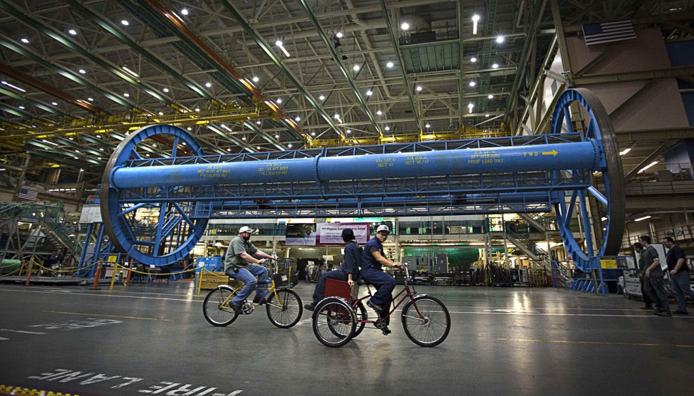 Workers use bicycles to move around the massive hangars at the Boeing assembly  operations in Everett
