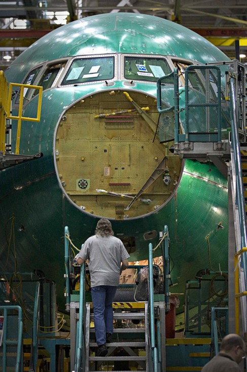 A worker prepares to work on the nose section of a Boeing 777 at the company's assembly plant in Everett