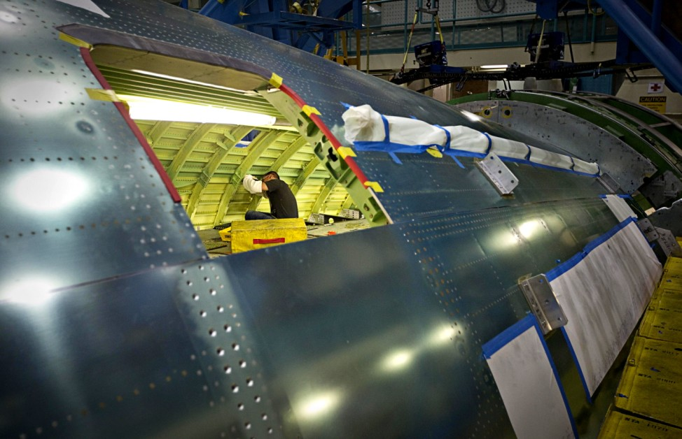 A worker makes adjustments inside the body of the Boeing 777 at their assembly plant in Everett