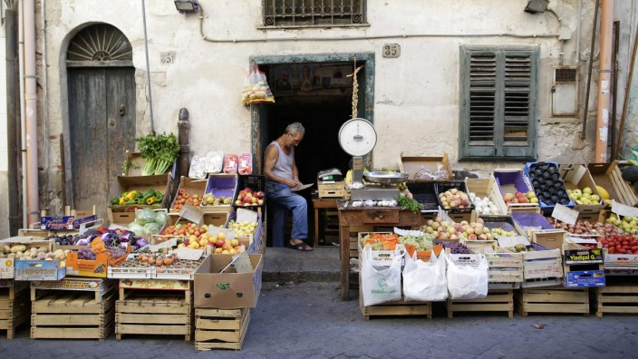 A fruit vendor waits for customers at a local market in the Sicilian town of Termini Imerese