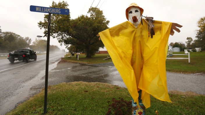 Vehicles pass a Halloween scarecrow fitted with a rain poncho as Hurricane Sandy hits Easton, Maryland