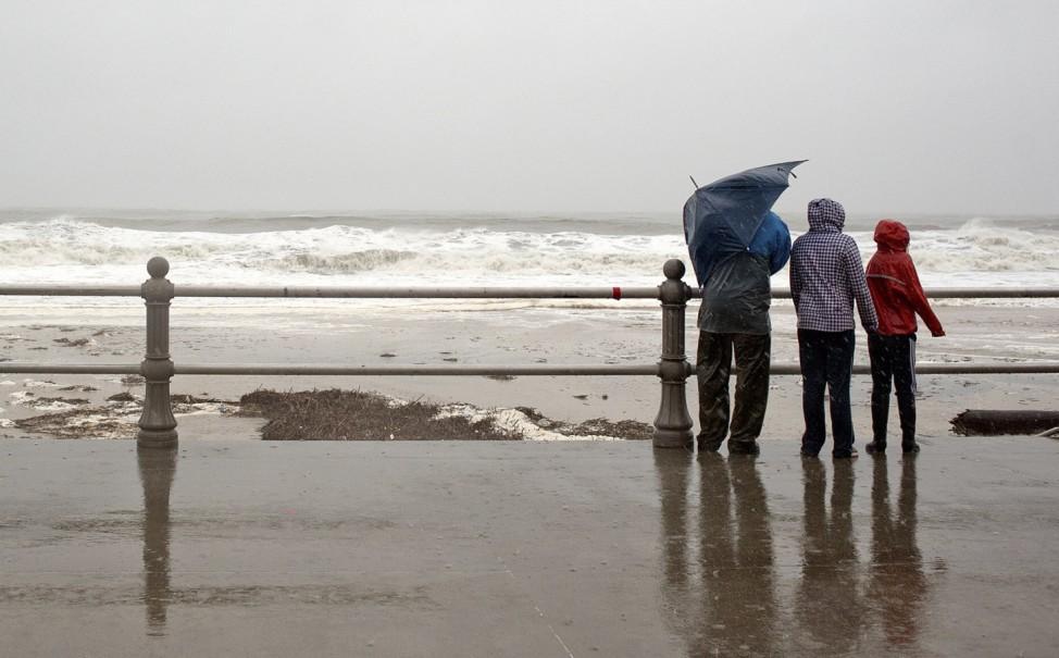 Pedestrians watch the high surf on Virginia Beach in Virginia Beach