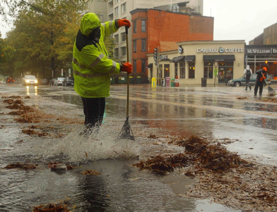 A public works employee attempts to keep storm drains clear of autumn leaves during Hurricane Sandy's approach in Washington