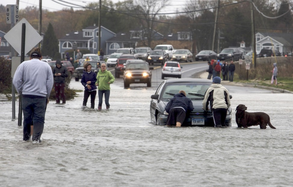 Pedestrians come to the aid of a motorist stuck on a flooded-out road along the shoreline area of Milford, Connecticut