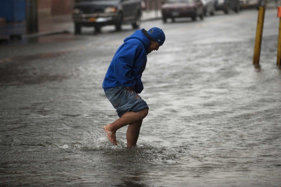 A man makes his way through flood waters in the Red Hook neighborhood of Brooklyn in New York
