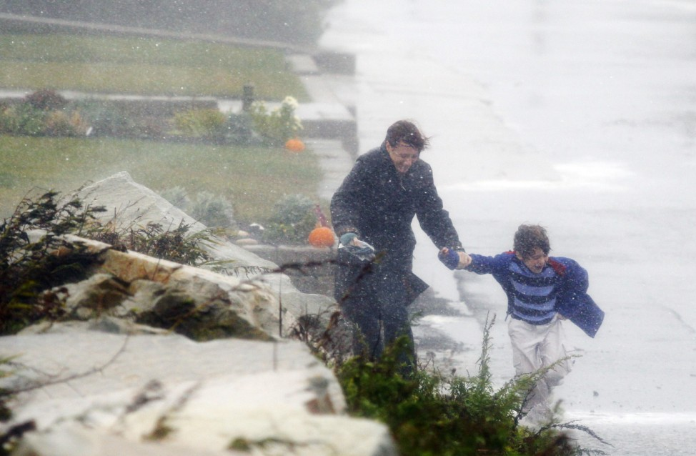 A woman holds the hand of her child as they run from their house to their car before the arrival of Hurricane Sandy in Scituate