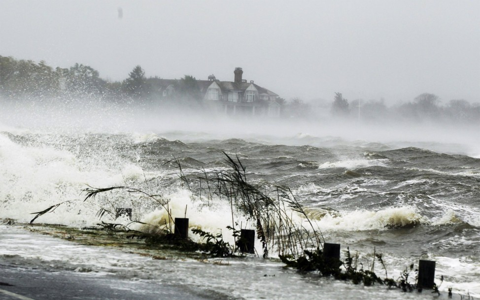Water driven onto a roadway by Hurricane Sandy breaks over a safety barrier in Southampton, New York