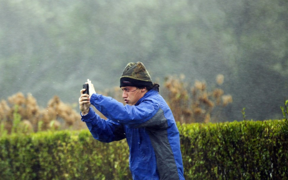 A man blown by wind from Hurricane Sandy attempts to take pictures of the storm in Southampton, New York