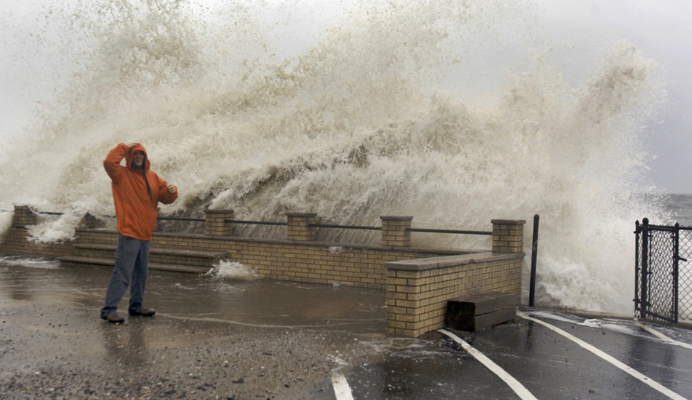 Waves crash over Mongirdas as the storm surge caused by Hurricane Sandy pummels the coastline in Milford, Connecticut