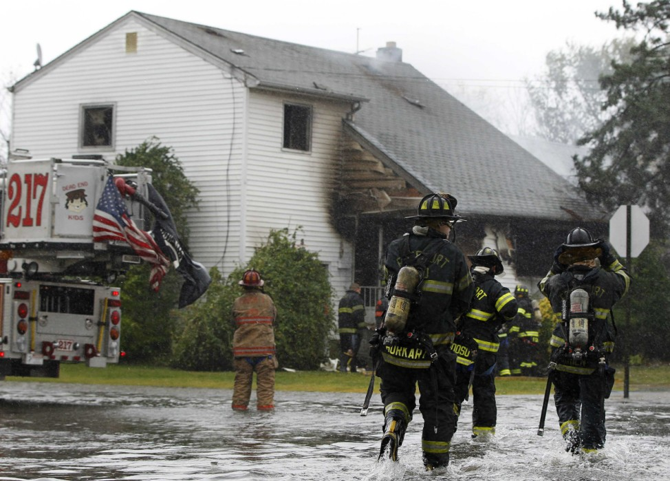 Members of the Freeport Fire Department respond to a house fire down a flooded street in Freeport
