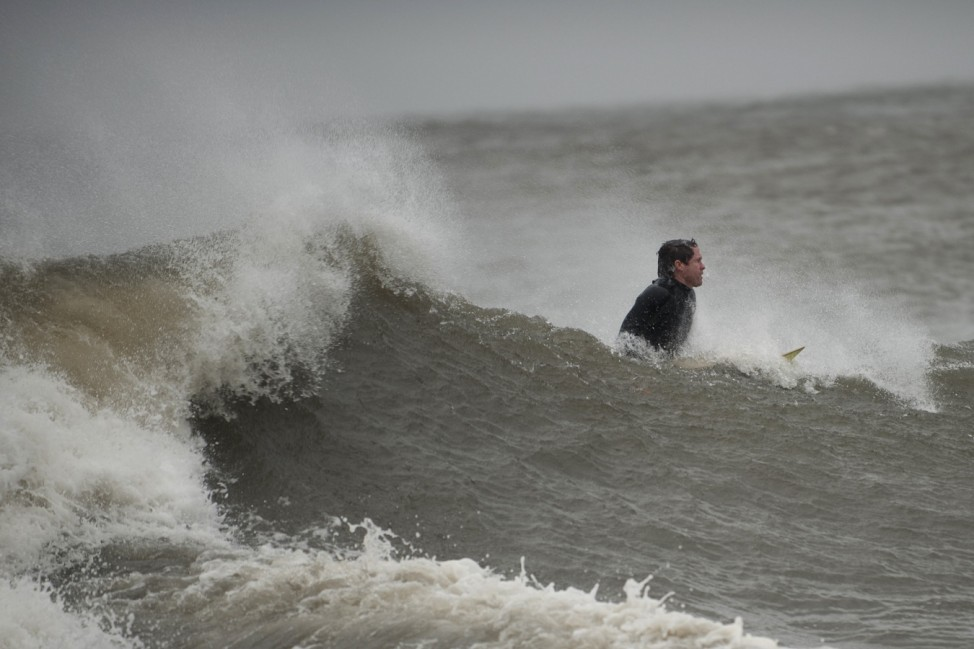 A surfer catches a wave along Coney Island in New York