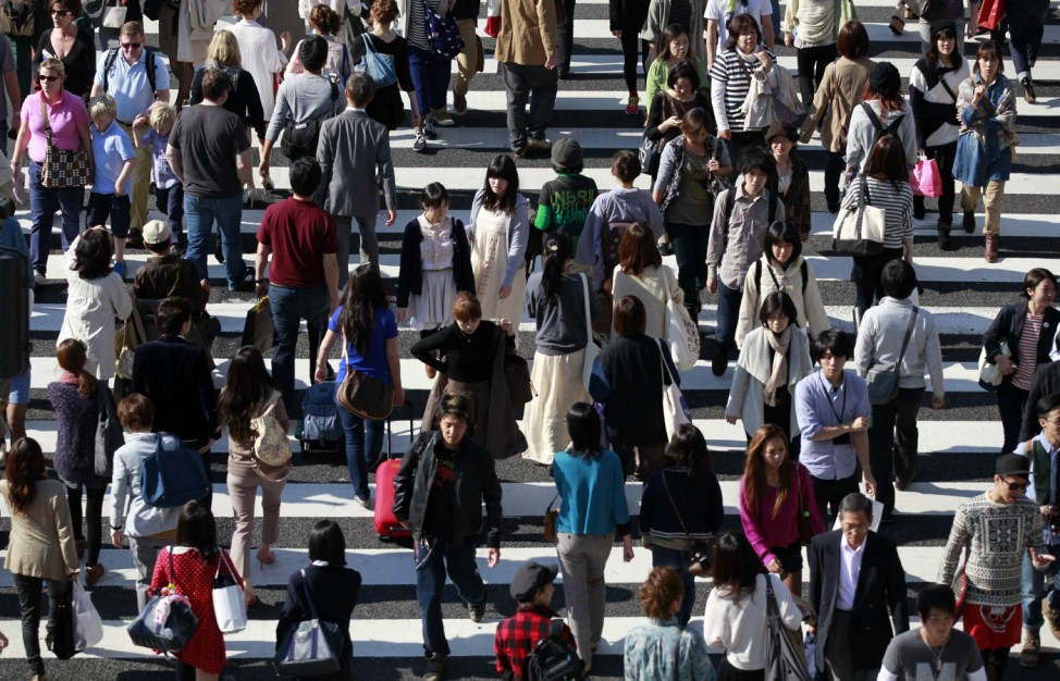 People cross a street in Tokyo's Harajuku shopping district